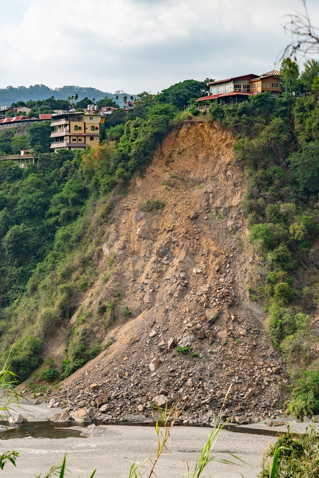 A modern house sits atop a cliff in a tropical environment. The cliff has recently had a landslide, with a large vertical scar of freshly-exposed brown soil and rocks piled up at its base.